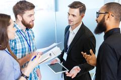 Young business people standing and talking with chief executive - stock photo
