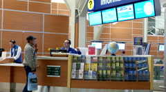 Man asking direction at informtion center inside YVR airport Stock Footage