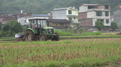 China agriculture, modern tractor plowing a rice field nearby village - stock footage
