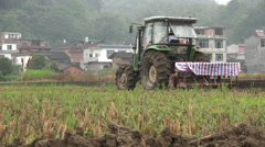 Rural China, farmer uses a tractor to plow the rice fields Stock Footage