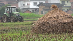 Stock Video Footage of A farmer uses a tractor to plow a rice field in a small village in China