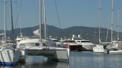 Stock Video Footage of A catamaran and other sailboats anchored in the port of Saint-Tropez