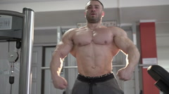 Stock Video Footage of The world champion of bodybuilding posing in the gym. Slowly
