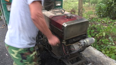 A driver cranks up the engine of an old pickup truck in rural China Stock Footage