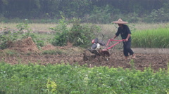 Farmer uses a motorized plow on a rice paddy field in rural China Stock Footage