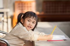 Asian children with yellow pencil in hand doing school home work with happine Kuvituskuvat