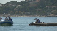 Wooden raft, swimmers, boat and jet skies on the sea in Sainte-Maxime, France Stock Footage
