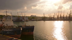 Tugboats anchored at Odessa harbor and big cranes sunset, zoom out  Stock Footage