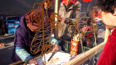 Traditional sugar painting craftsman makes a sugar monkey on a temple fair Stock Footage