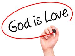 Man Hand writing God is Love with black marker on visual screen Stock Photos