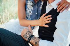 girl and serious man with a tattoo on his arm - stock photo