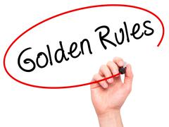Man Hand writing Golden Rules with black marker on visual screen Stock Photos