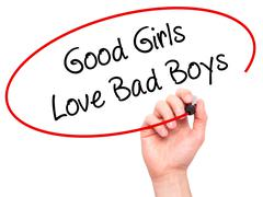 Man Hand writing Good Girls Love Bad Boys with black marker on visual screen Stock Photos