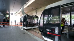 Tourists prepare to ride inside a cable car, above the Rhine river. Stock Footage