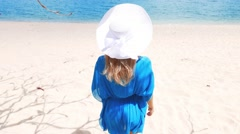 Young beautiful women in the blue tunic on the sunny tropical beach Stock Footage