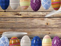 Easter eggs and bird feathers on wood background with space Stock Illustration
