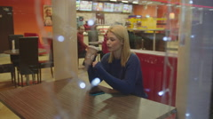 Young Woman Waiting for Somebody in Coffeehouse Stock Footage