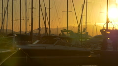 People walking next to sailboats anchored in Saint-Tropez at sunset Stock Footage