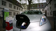 Electro car is charging in the street. - stock footage