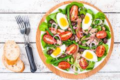 Homemade salad nicoise with tuna, anchovies, tomatoes - stock photo