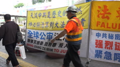 People walk past protest banners of Falun Gong movement in Hong Kong Stock Footage