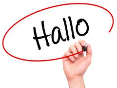 Man Hand writing Hallo  (Hello in German) with black marker on visual screen - stock photo