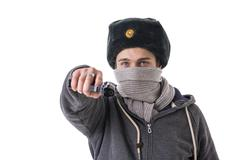 Man in winter hat and scarf threatening with gun Stock Photos