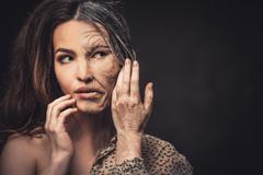 Aging and skin care concept. Half old half young woman. Stock Photos