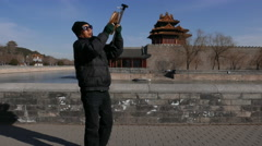 Man flying kite beside gate tower of Forbidden city Stock Footage