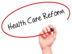 Man Hand writing Health Care Reform with black marker on visual screen - stock photo