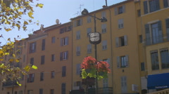 A street clock and flowers on a sunny day in Grasse Stock Footage