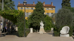 Statue of Fragonard and a passageway through trees in Grasse Stock Footage