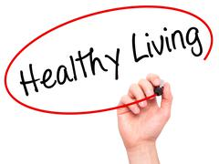 Man Hand writing Healthy Living  with black marker on visual screen Stock Photos