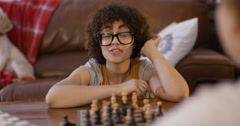 4K Young woman & little girl playing chess at home Stock Footage