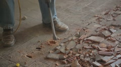 Worker with a sledgehammer on floor tiles Stock Footage