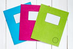 Three colored exercise books Stock Photos