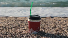 Bright paper cup of coffee on a sandy beach. Seashore Stock Footage