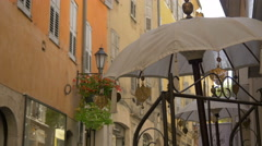 A white umbrella with gilded decorations on a street in Grasse - stock footage