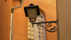 Vintage lamp with a wrought iron sign on a street in Grasse Stock Footage