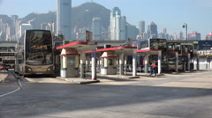 Stock Video Footage of Bus station at Tsim Sha Tsui in Kowloon, opposite the skyline of Hong Kong