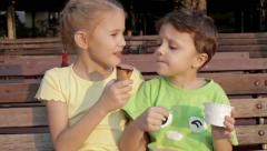 Two happy children eating ice cream in the park at the day time. Stock Footage
