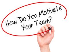 Man Hand writing How Do You Motivate Your Team? with black marker on visual s - stock photo