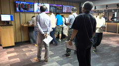 Chinese men place bets on their favorite horse at the racecourse in Hong Kong Stock Footage