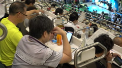 Chinese men keep scores during horse race at Hong Kong Jockey Club Stock Footage