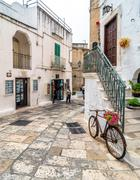 typical white street with bicycle in Ostuni, Italy - stock photo