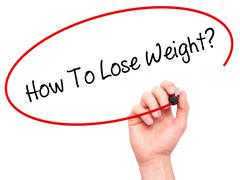 Man Hand writing How To Lose Weight? with black marker on visual screen Stock Photos