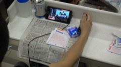 Keeping live scores of a horse race on smartphone, at the tracks in Hong Kong Stock Footage