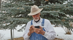Old man coveralls floppy cowboy hat grey goatee frustrated with smart phone Stock Footage