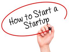 Man Hand writing How to Start a Startup with black marker on visual screen Kuvituskuvat