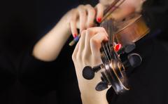 Woman's hands playing the violin Stock Photos